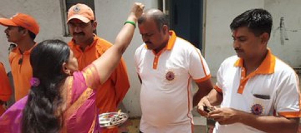 Tying rakhis to workers and helpers